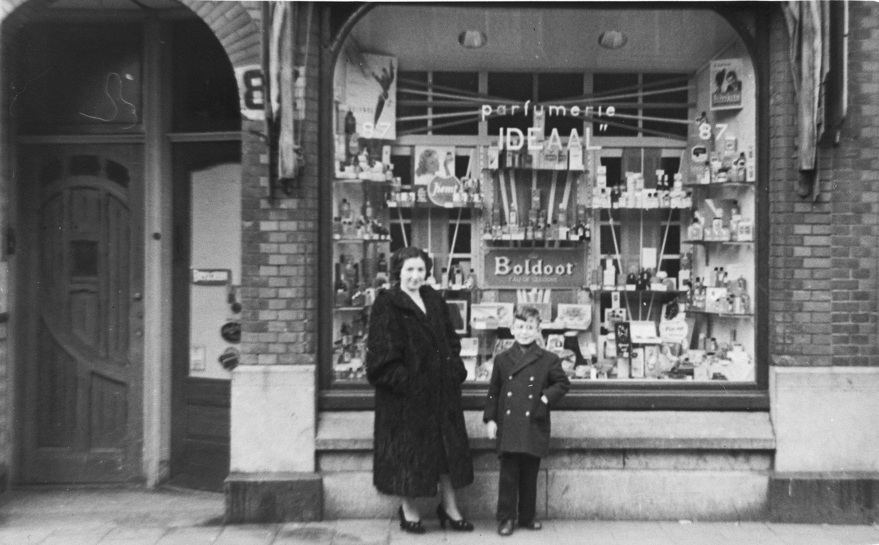 Gitel and Alfred Münzer pose in front of their cosmetics store in The Hague.