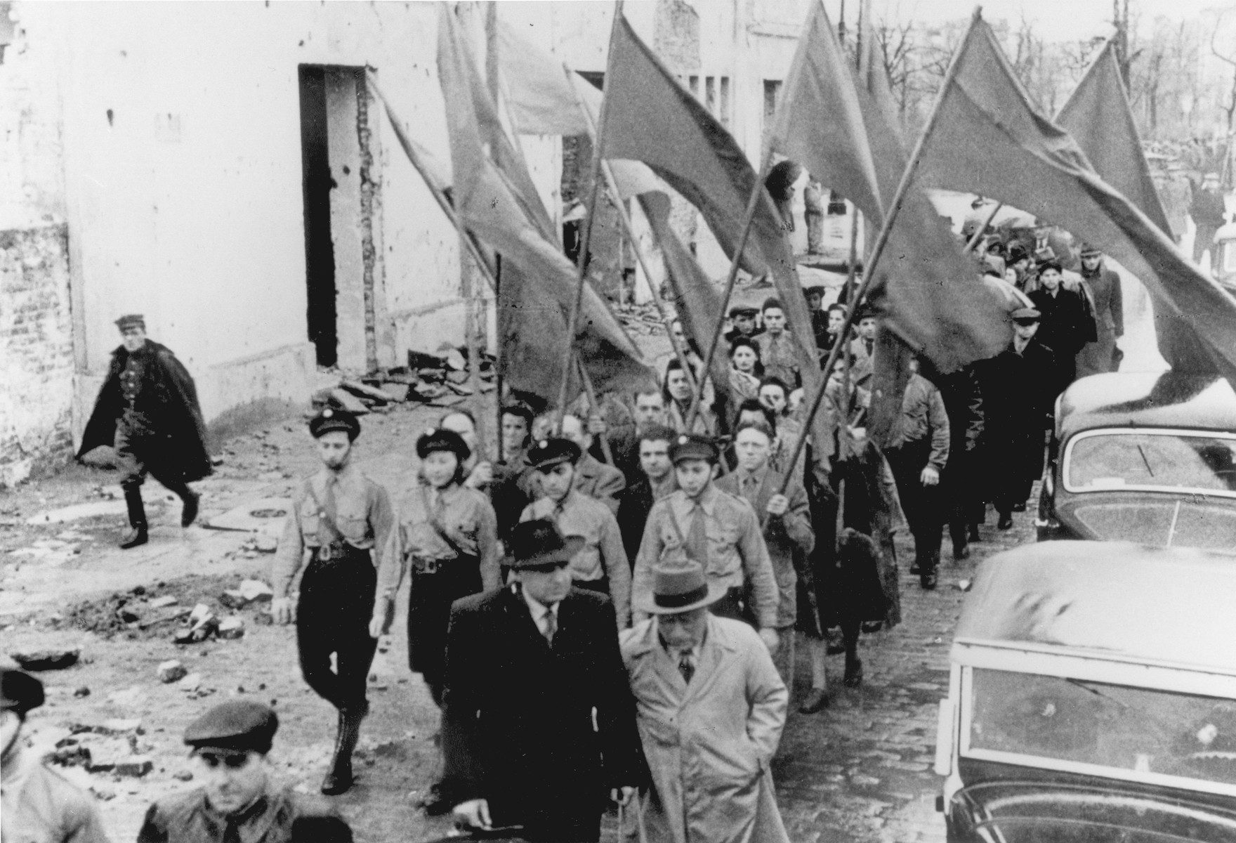 Jewish survivors carrying flags march along a street in Warsaw [probably during a demonstration marking the fourth anniversary of the Warsaw ghetto uprising].   The marchers are probably members of the Betar revisionist Zionist movement.