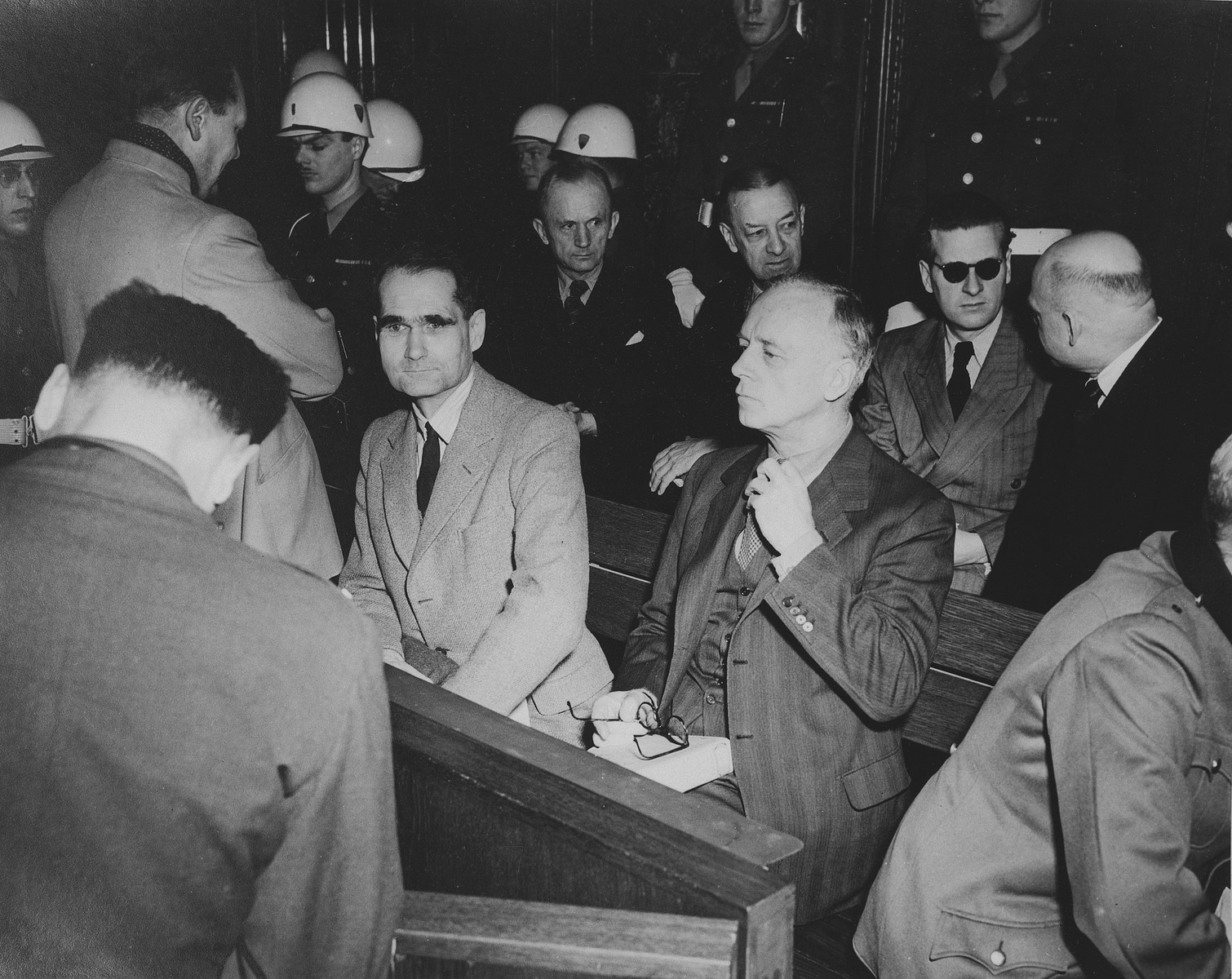 The defendants in the dock at the International Military Tribunal trial of war criminals at Nuremberg.  Pictured in the front row from left to right are: Hermann Goering (back turned), Rudolf Hess and Joachim von Ribbentrop.  Pictured in the back row are Karl Doenitz and Erich Raeder (both behind Hess).