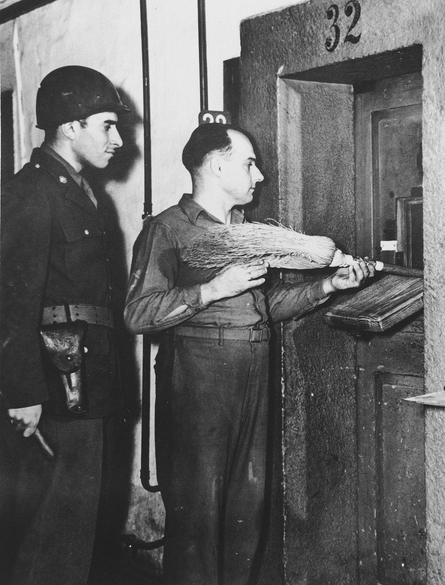 A guard pushes a broom through the grating of the prison cell of one of the defendants in the International Military Tribunal trial of war criminals at Nuremberg.