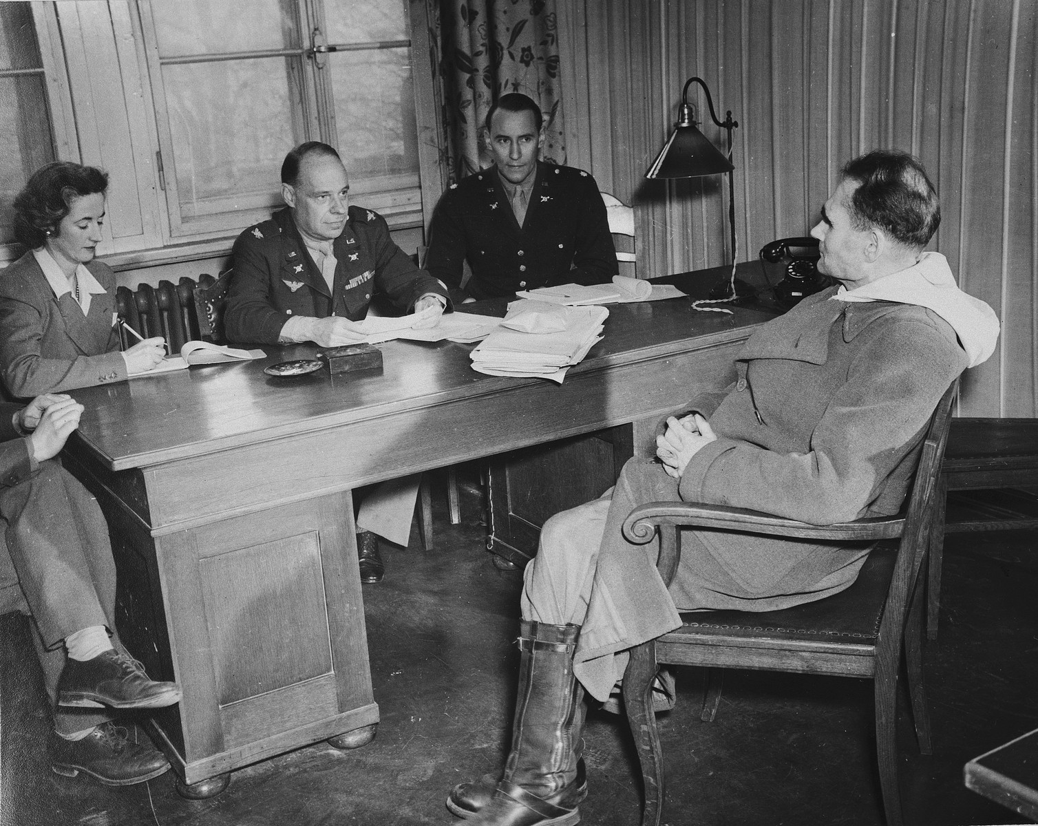 IMT defendant Rudolf Hess speaks to a lawyer or prosecutor in Nuremberg.