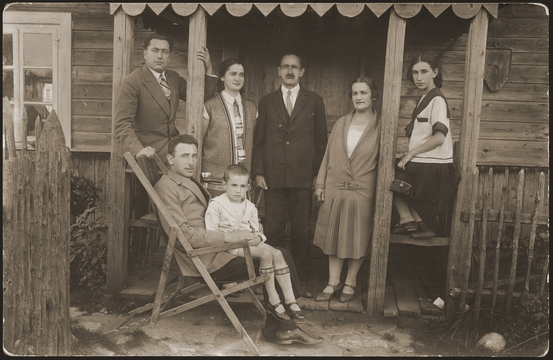 The Dworzecki family poses on the porch of their summer cottage in Molczadz.  Pictured standing from right to left are: Wita, Helena and Jakub Dworzecki.  Lulek Dworzecki sits in the lap of an unidentified relative.