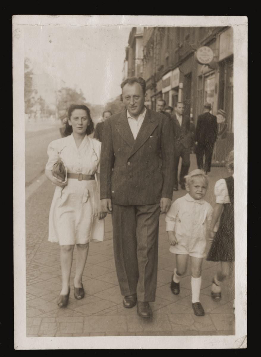 Zishe Malah walks down a street in Poland with his wife Miriam and two unidentified children.  His wife sewed her dress out of a sheet.