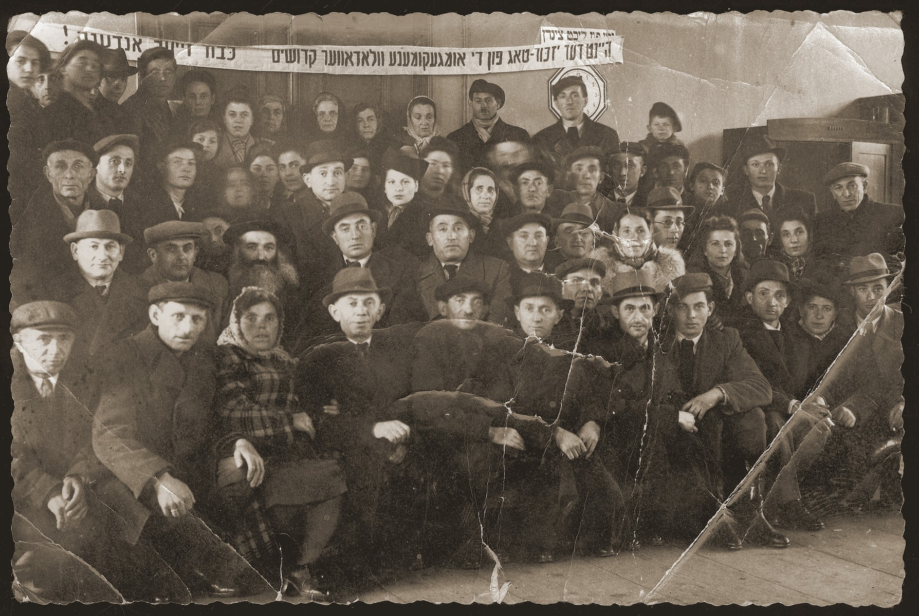 Group portrait of Jewish DPs taken at a memorial service commemorating the anniversary of the murder of the Jews of Wlodawa.   Jehoshua Glincman is sitting in the second row from the bottom, fifth from the left.  He was known as Yusha/Yasha, his Polish/Russian names and he survived the camps with his brother.  During the war, he lived in the Wlodawa ghetto and worked as a prisoner at Adampol Arbeitslager and Sobibor.  He and his brother survived, recuperated at the DP camp in Berlin, and Jehoshua later testified at the trial of the Nazis in charge of the Wlodowa ghetto, Adampol Arbeitslager and Sobibor.