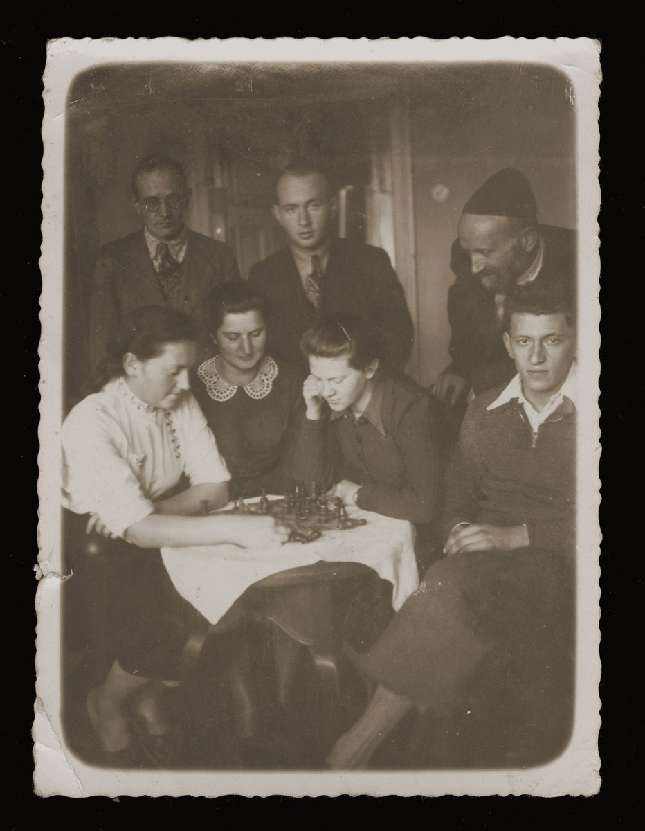 Members of the Feder family gather around a chess game.  Pictured sitting from left to right are: Rachel Feder, Shoshana ?, Itka Feder and Velvel Malach.  Standing are Mosze Feder, Yehiel Feder and Abraham Yitzhak Feder.