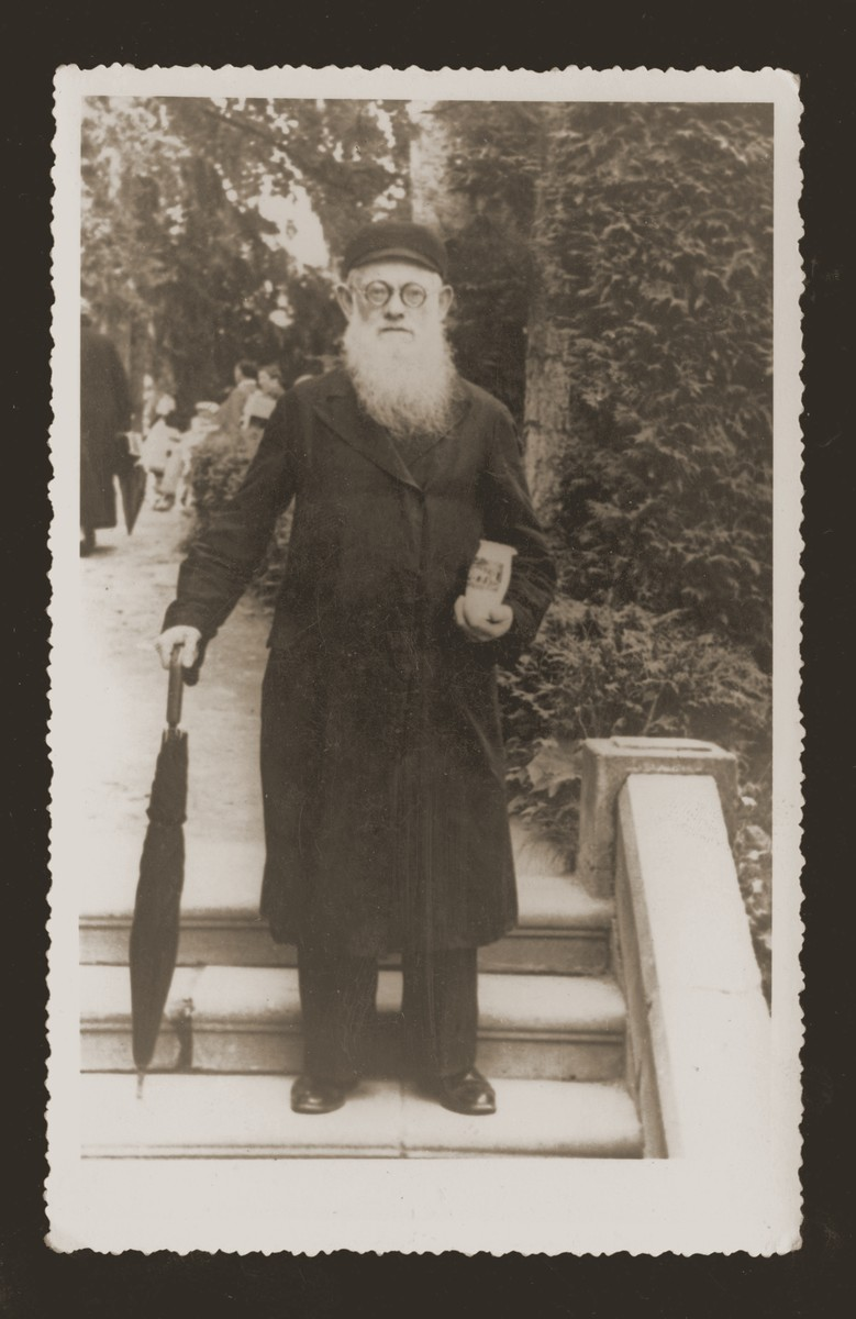 Mr. Wilder, the father of Pola Malach, carries a small pitcher and an umbrella while on vacation at a spa.