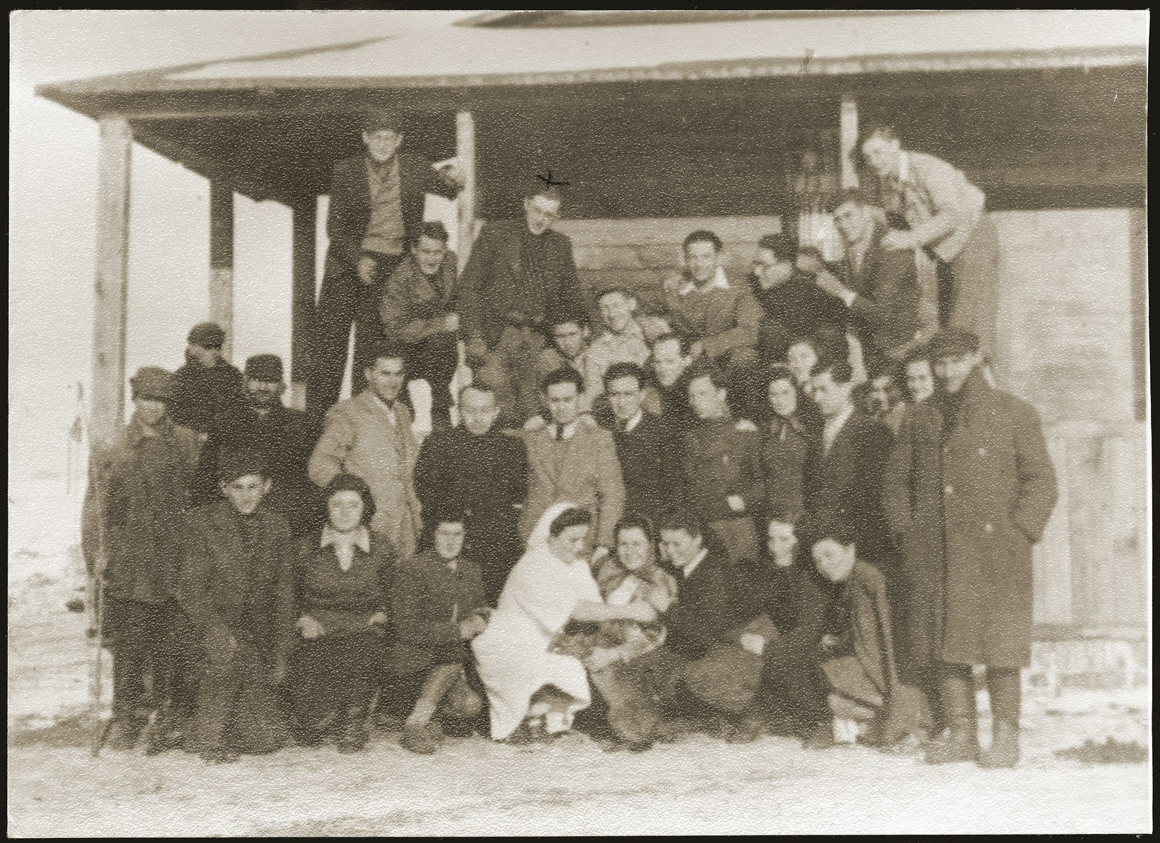 "Group portrait of Jewish youth living at the ""Farma"" Zionist agricultural collective.  The ""Farma"" was a  plot of land between Bedzin and Sosnowiec that was allocated to the local Zionist youth movements by the Jewish Council for the growing of vegetables. The youth movements created a hachshara on the site.  Soon after, the ""Farma"" became the center of resistance efforts, as well as youth activity, in the ghetto."