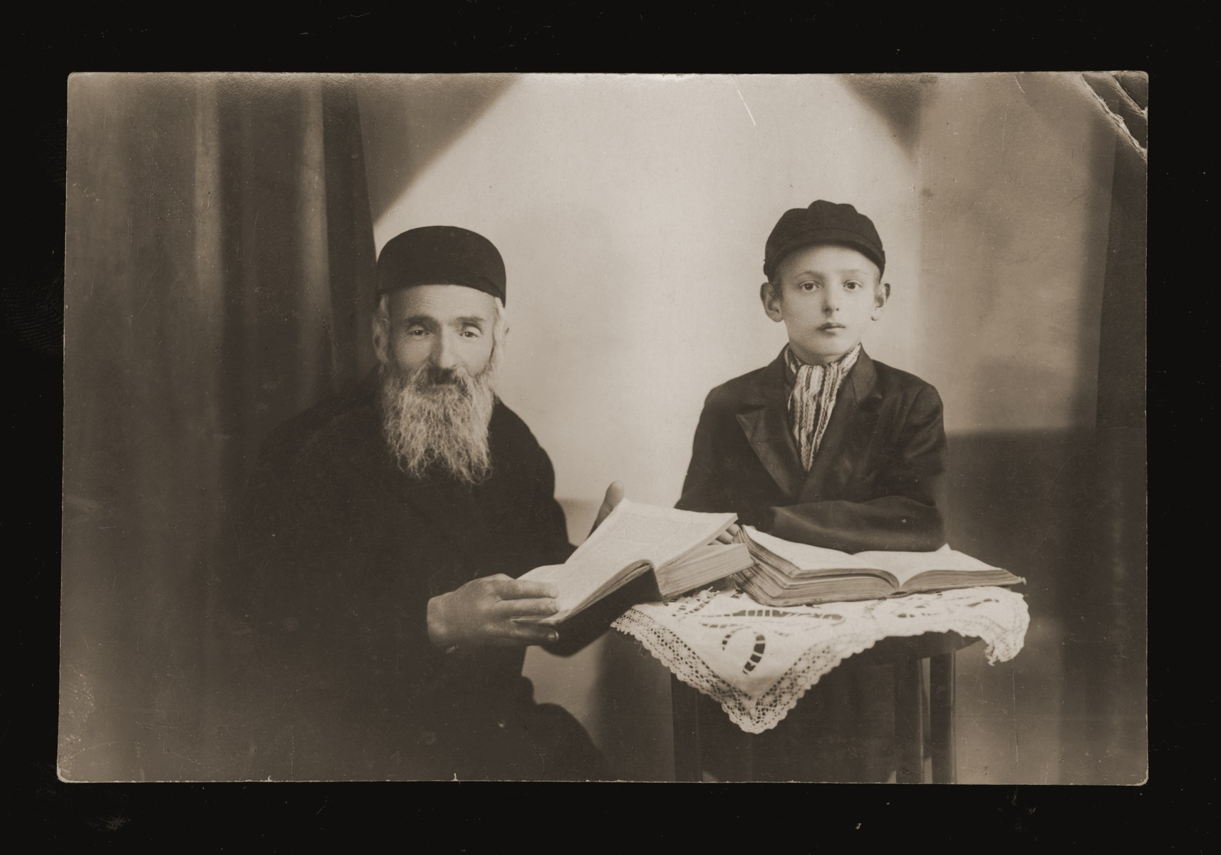 Portrait of an eldery Jewish man studying a religious text with a young boy.