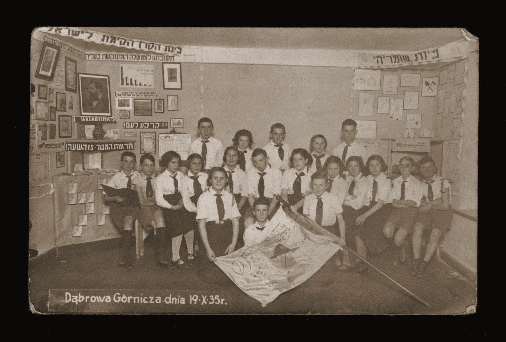 Members of the Hashomer Hatzair Zionist youth group in Dabrowa pose with a flag before a display about the Keren Kayemet [Jewish National Fund].  Among those pictured is Yisroel Miodownik (top row, left) and Esther Malach (holding the flag pole).