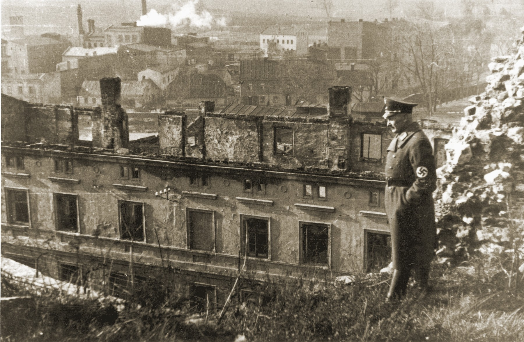 An SS officer surveys the destruction of an apartment house on Zumkowa Street.  Yehiel Hershokowitz lived in this building.