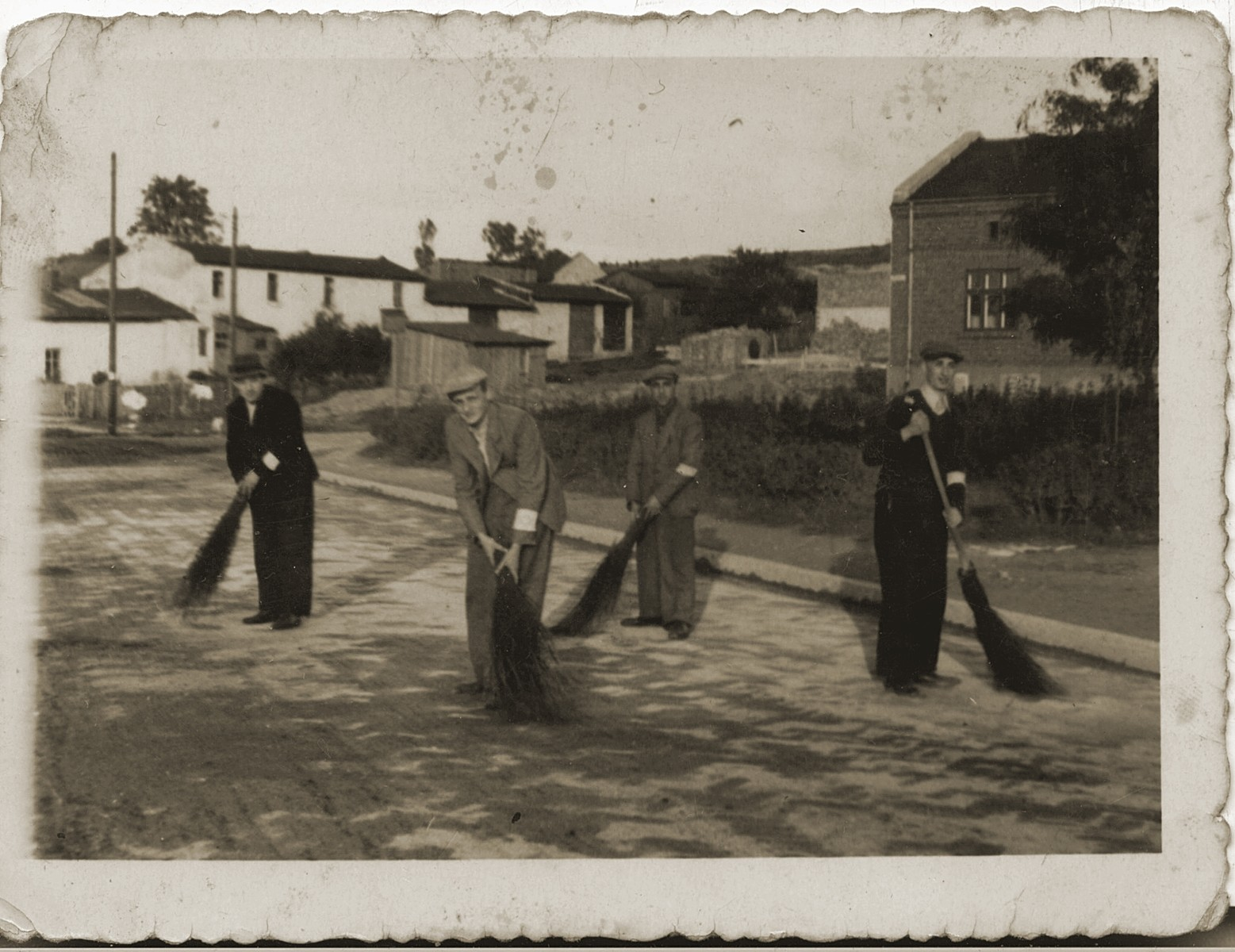Jews wearing armbands are forced to sweep a street.