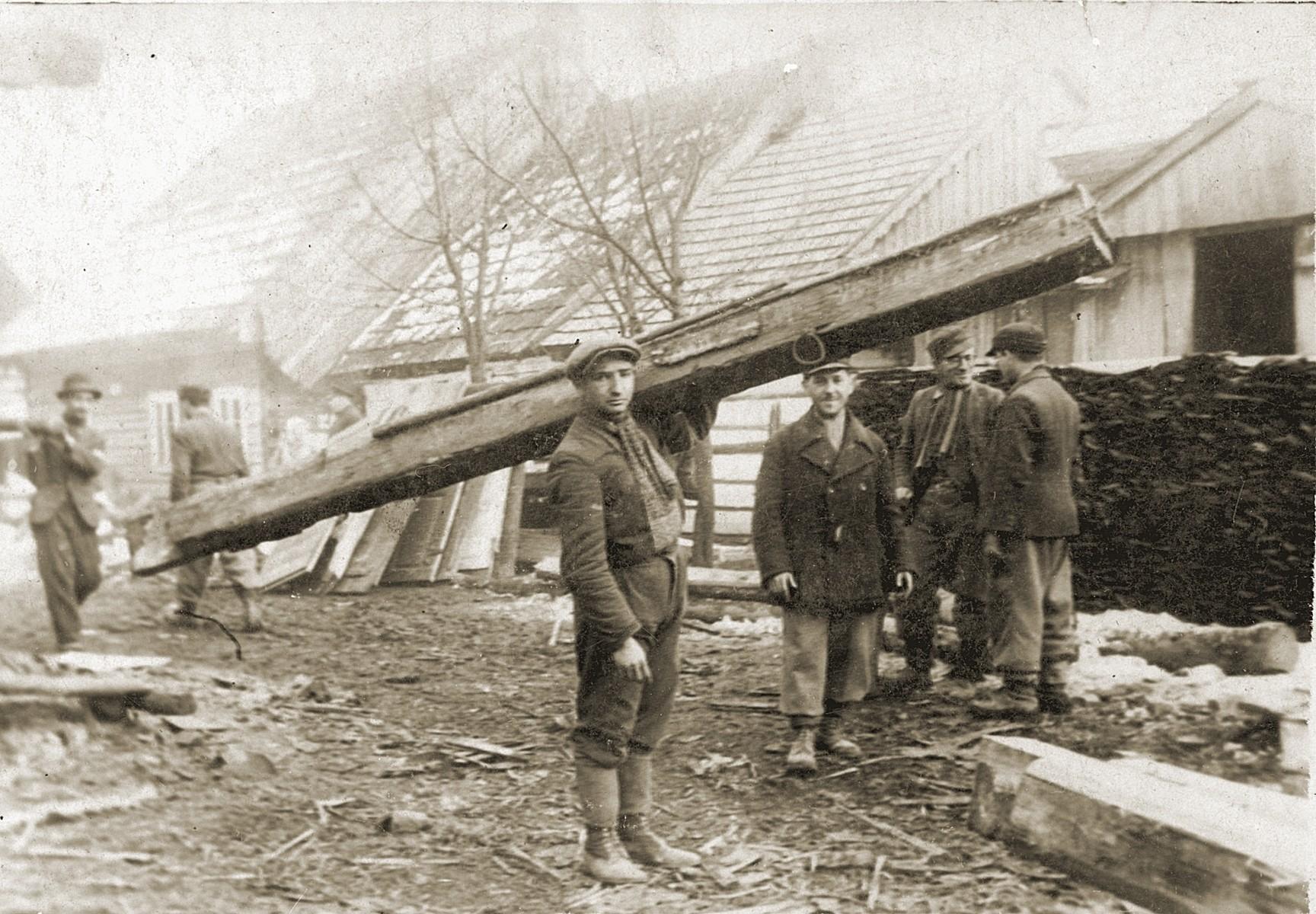 Jewish men, originally from Bedzin, work in the lumberyard of a German labor camp.