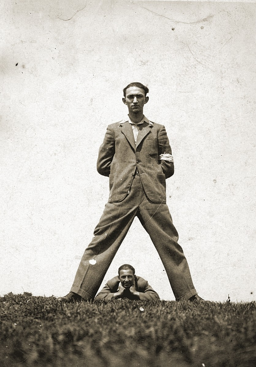 Szmulek Lustiger lies on the ground beneath a friend in a humorous pose in the Bedzin ghetto.