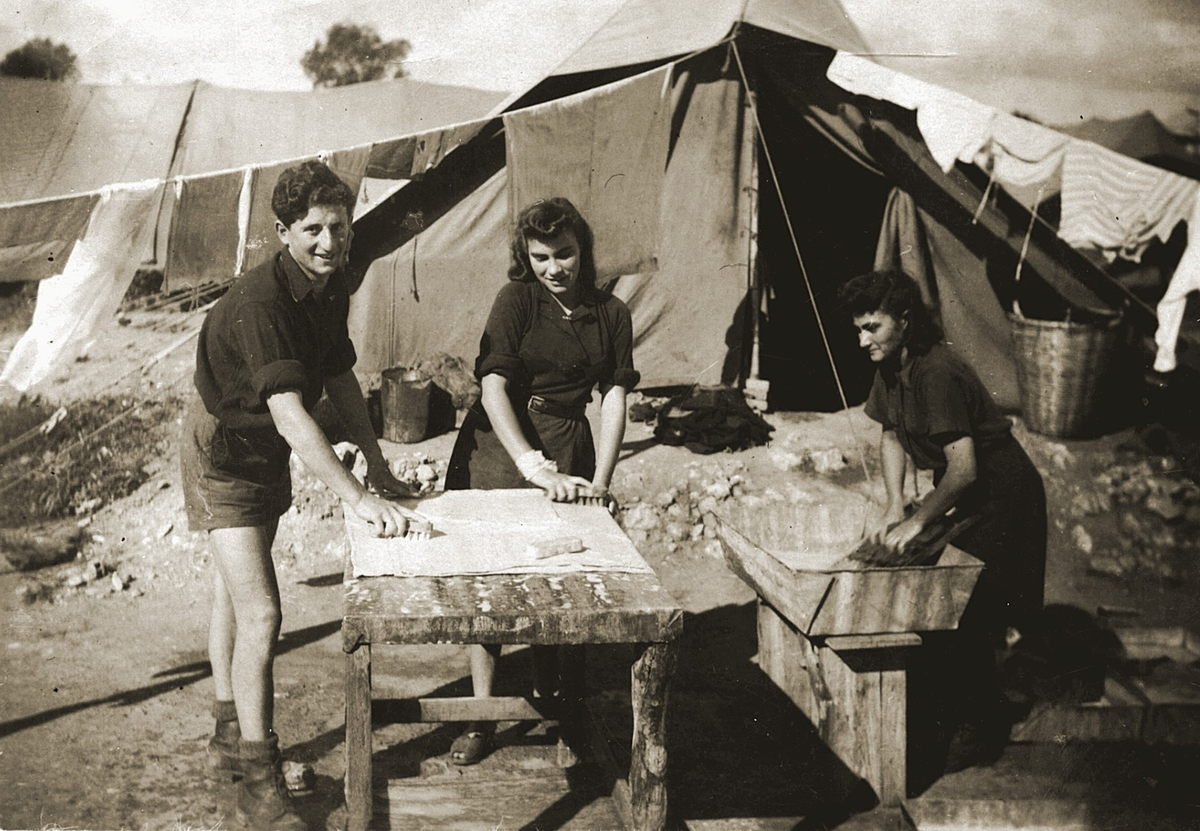 Aharon Zelmanovicz, Blanca Kuklinska and Chana Zelmanovicz do their laundry on a table outside a tent in the Cyprus summer Camp 55.