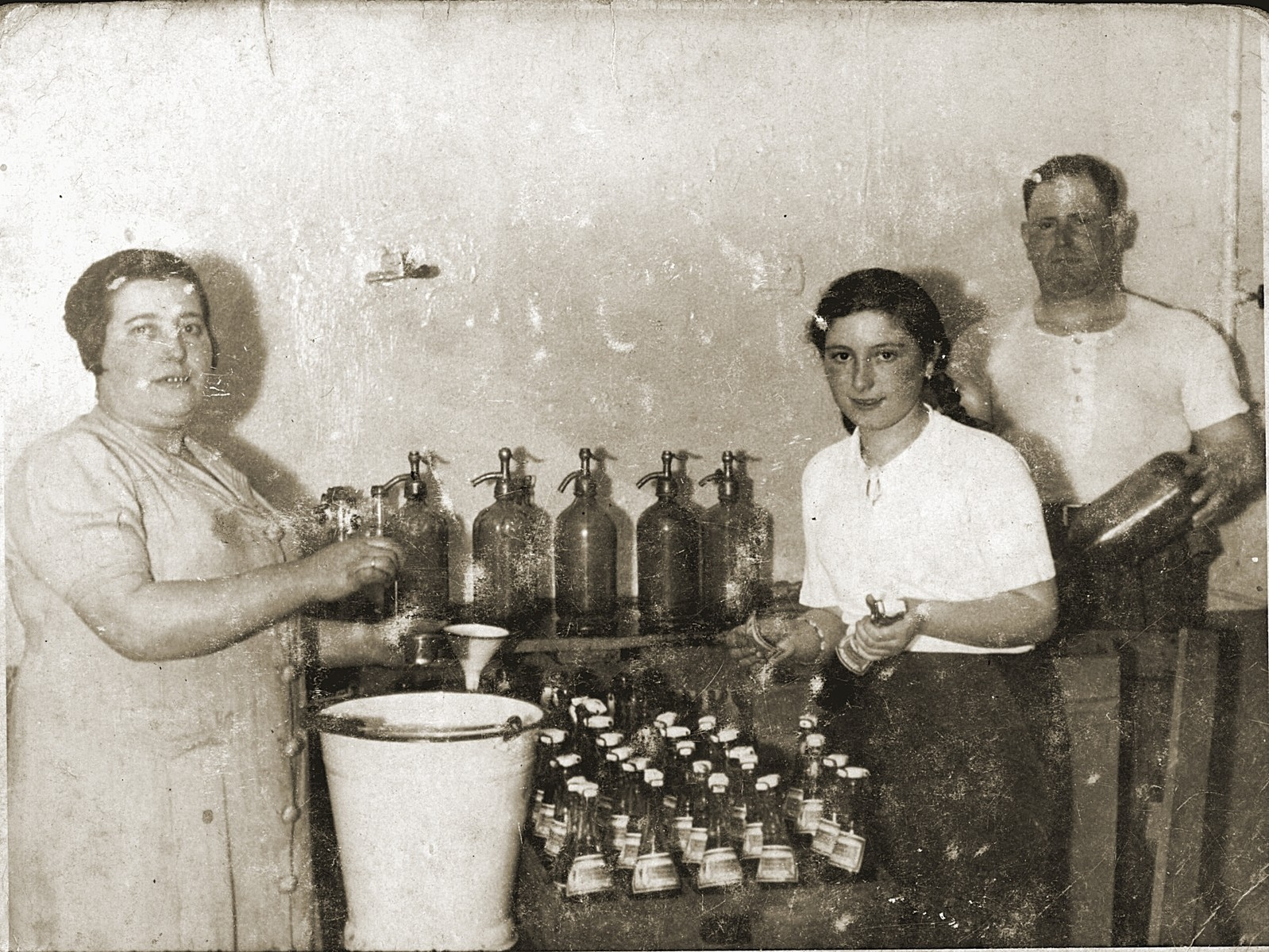 The Cawadel family fills bottles of soda in their factory.  From left to right are Kayla Puterschnit Cawadel, Mania Cawadel and Wolf Cawadel.