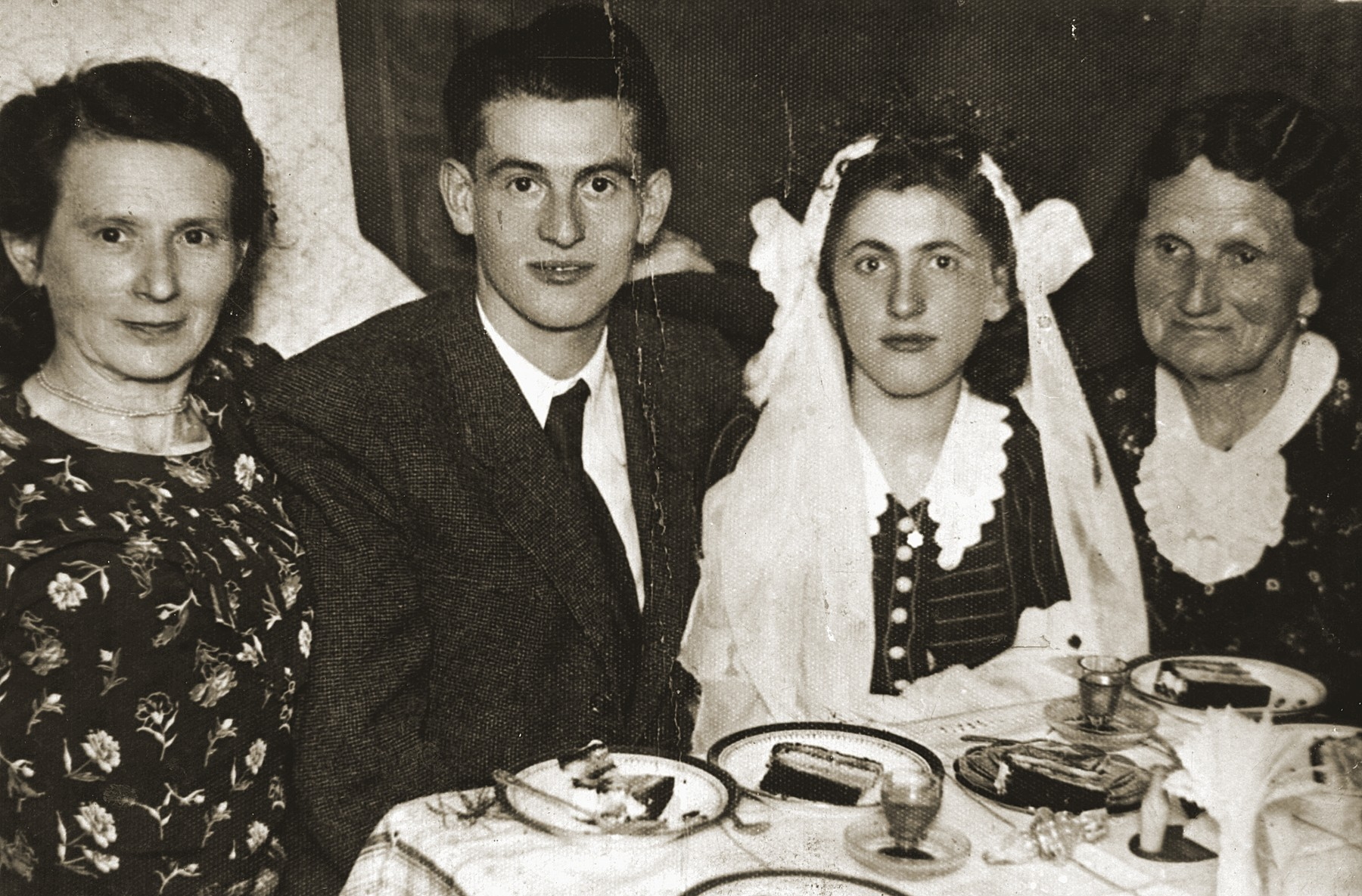 Yaakov and Mania Muszynski celebrate their wedding in the Bedzin ghetto.  Pictured from left to right are Hinda Foxbroomer, Yaakov Muszynski, Miriam Hassenberg Muszynski, and Hana Muszynski.