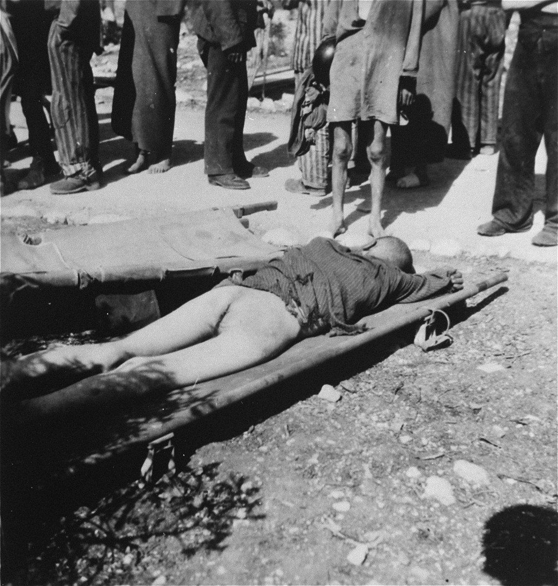 A corpse lies on a stretcher in the Ebensee concentration camp.