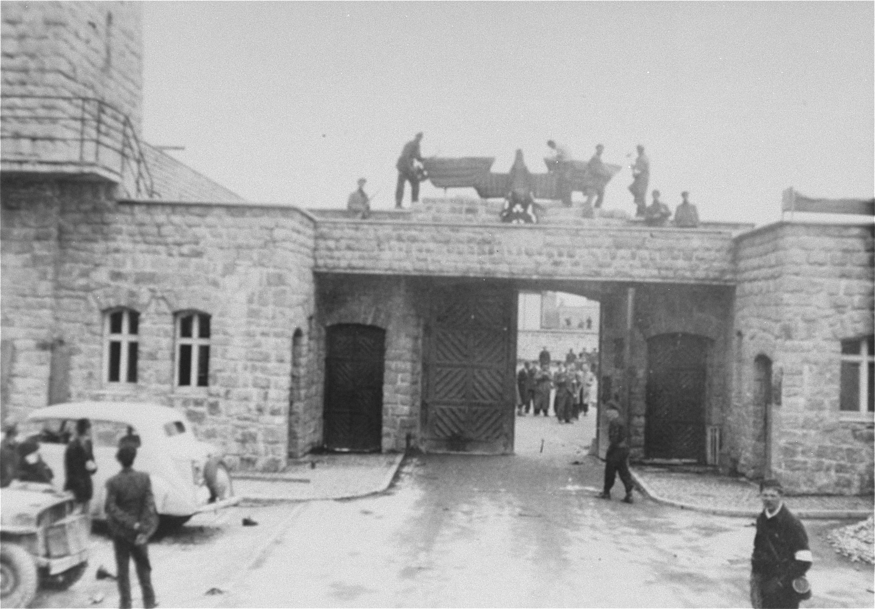 Survivors take down the Nazi eagle that hangs above the entrance to the SS compound in Mauthausen on the day of liberation.    The white car belongs to the Red Cross.  A Red Cross representative and two German SS officers arrived at the camp in this car to surrender Mauthausen to the U.S. Army.