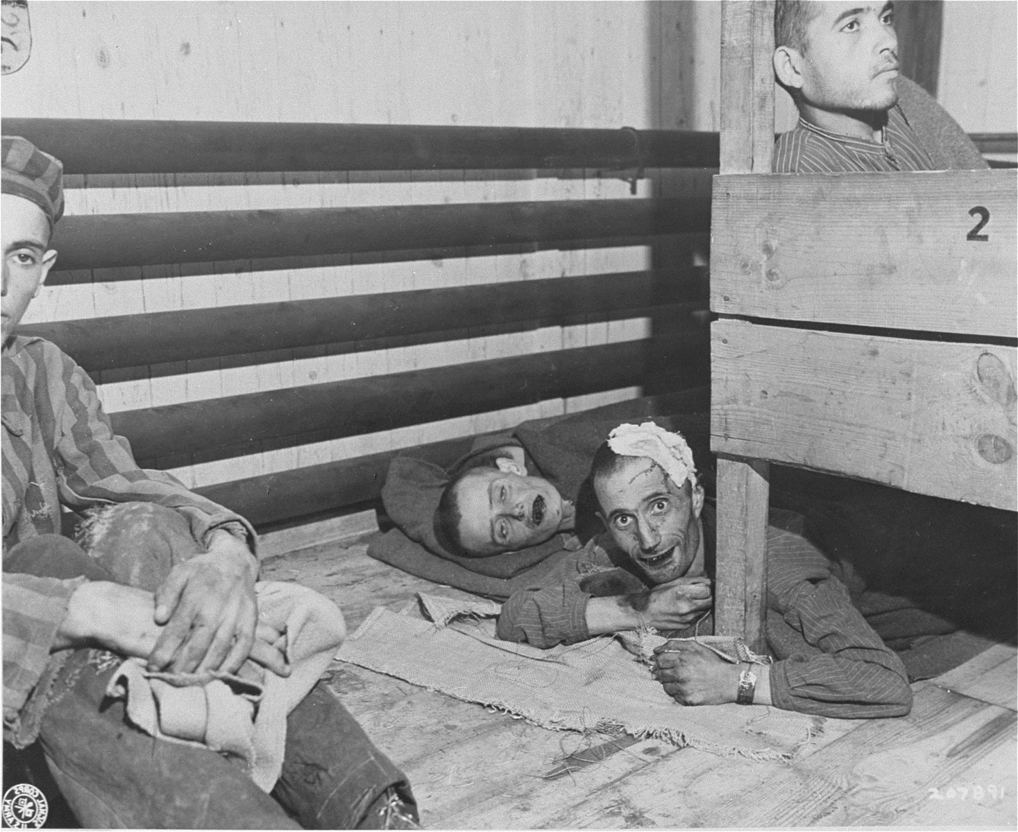 Survivors in the infirmary barracks for Jewish prisoners in the Ebensee concentration camp.  Those people who did not fit in the bunks were forced to sleep on the floor.
