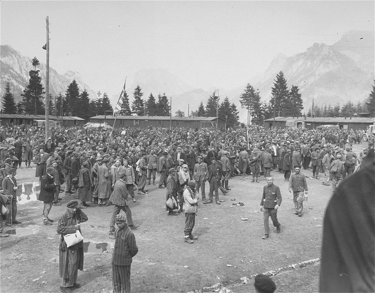 A large crowd of survivors congregates in the former roll call area of the Ebensee concentration camp.