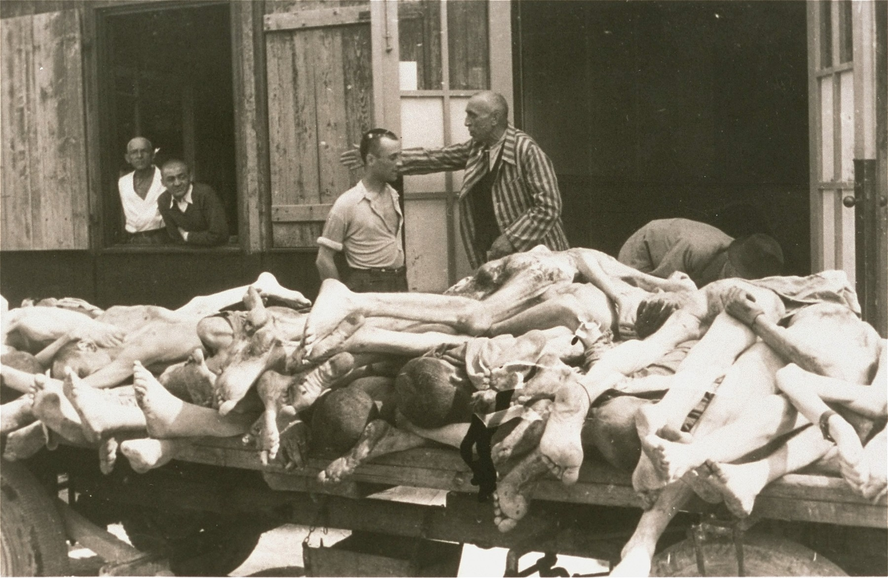 Survivors converse behind a cart loaded with the bodies of former prisoners at the Ebensee concentration camp.