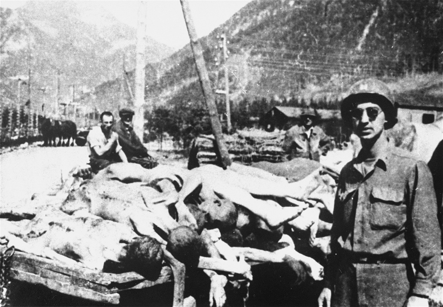 An American soldier, Captain Al Winters, poses next to a wagon loaded with the bodies of former prisoners at the newly liberated Ebensee concentration camp.