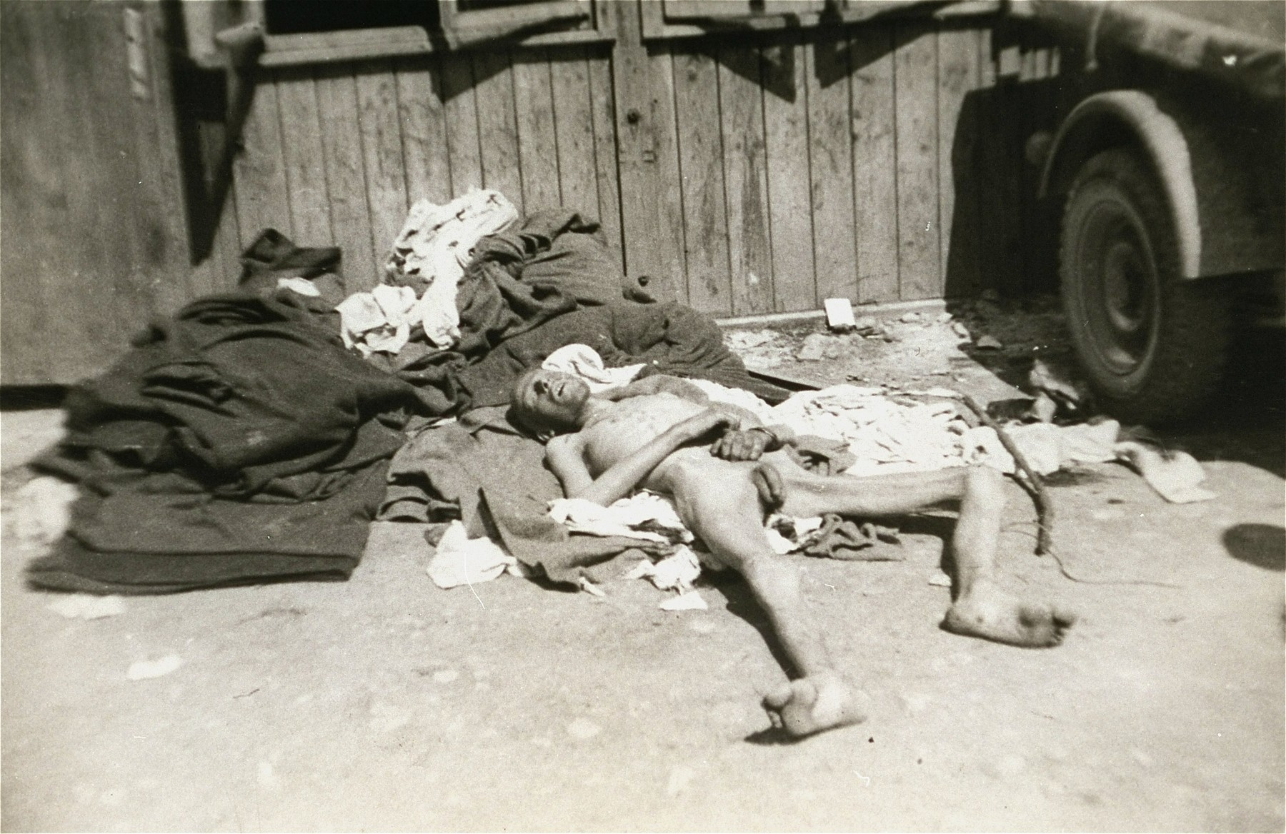 A former prisoner lies outside a barracks in the newly liberated Ebensee concentration camp.  It is not clear if he is alive or dead.
