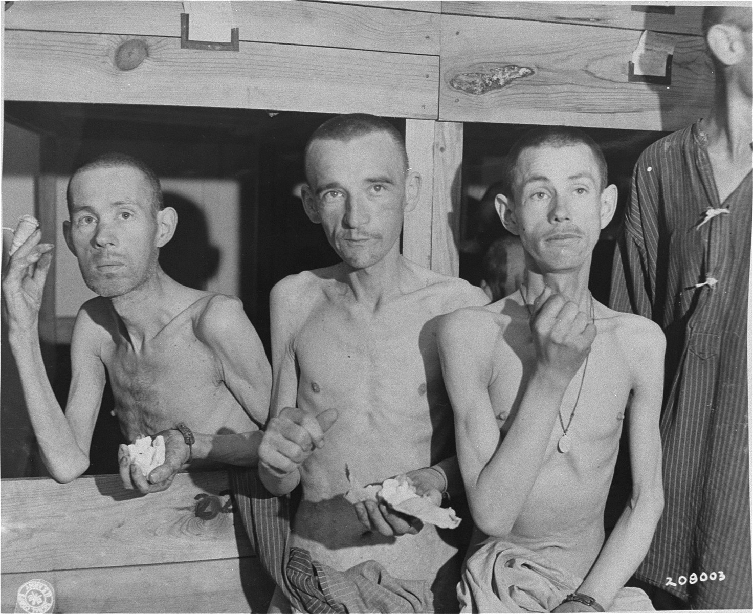 Three survivors suck on sugar cubes provided by American soldiers in the infirmary barracks for non-Jewish prisoners in the Ebensee concentration camp.