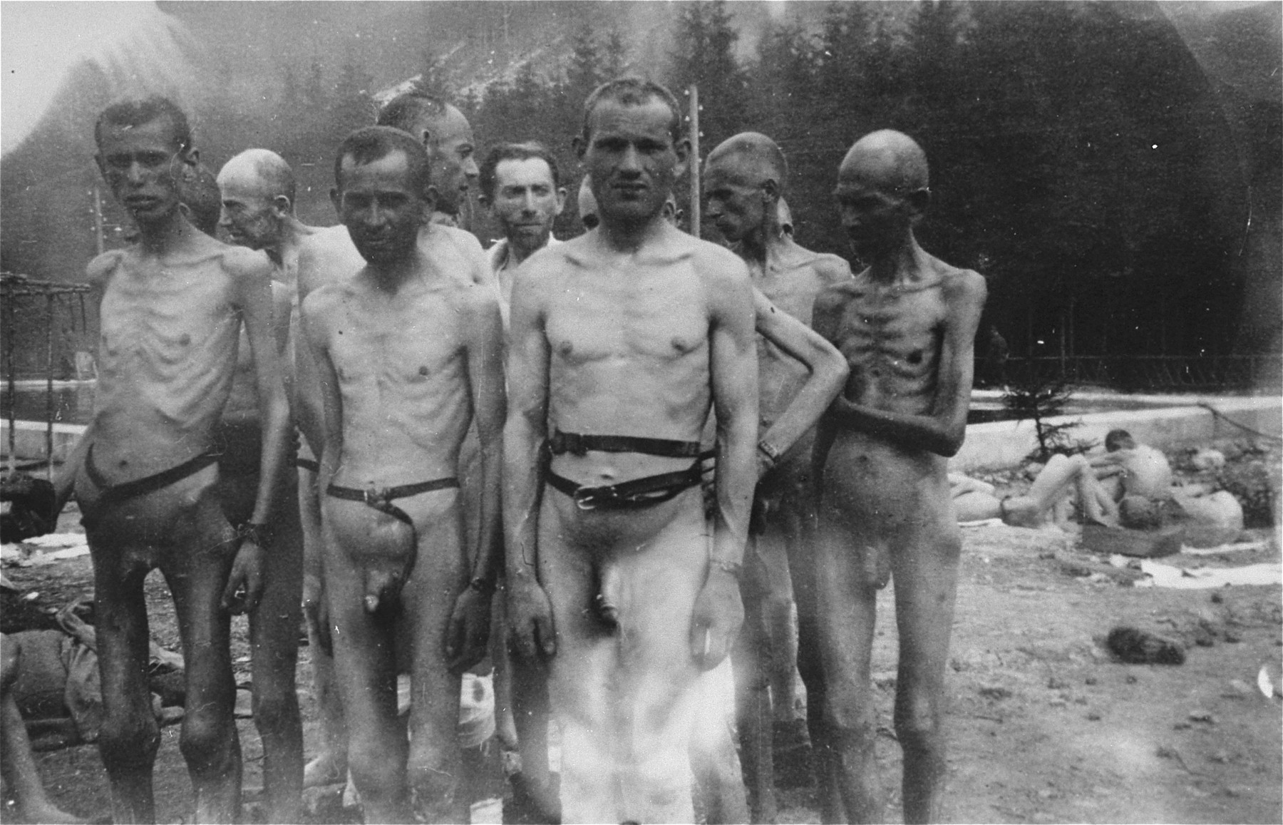 A group of emaciated Jewish survivors stand outside in the Ebensee concentration camp.