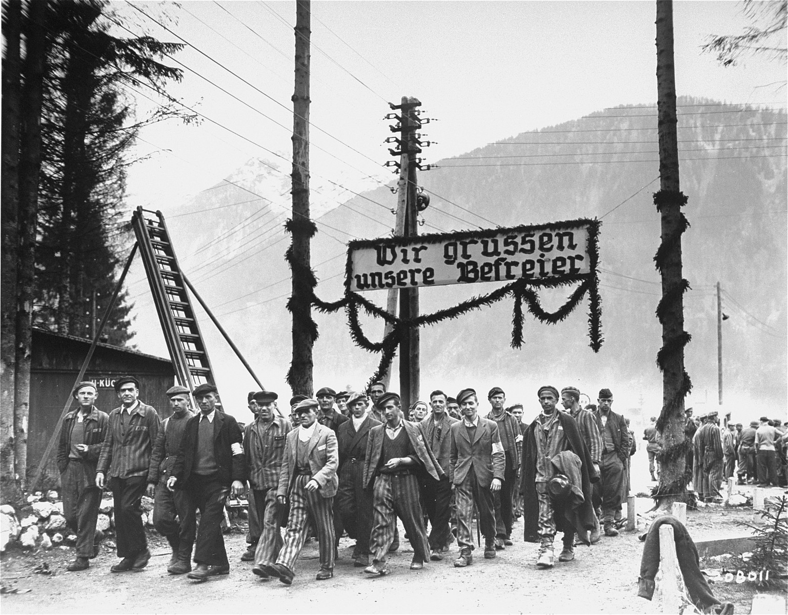 """Survivors of the Ebensee concentration camp, who were liberated by U.S. Third Army troops, march out of the camp beneath the sign, """"We Welcome Our Liberators."""""""