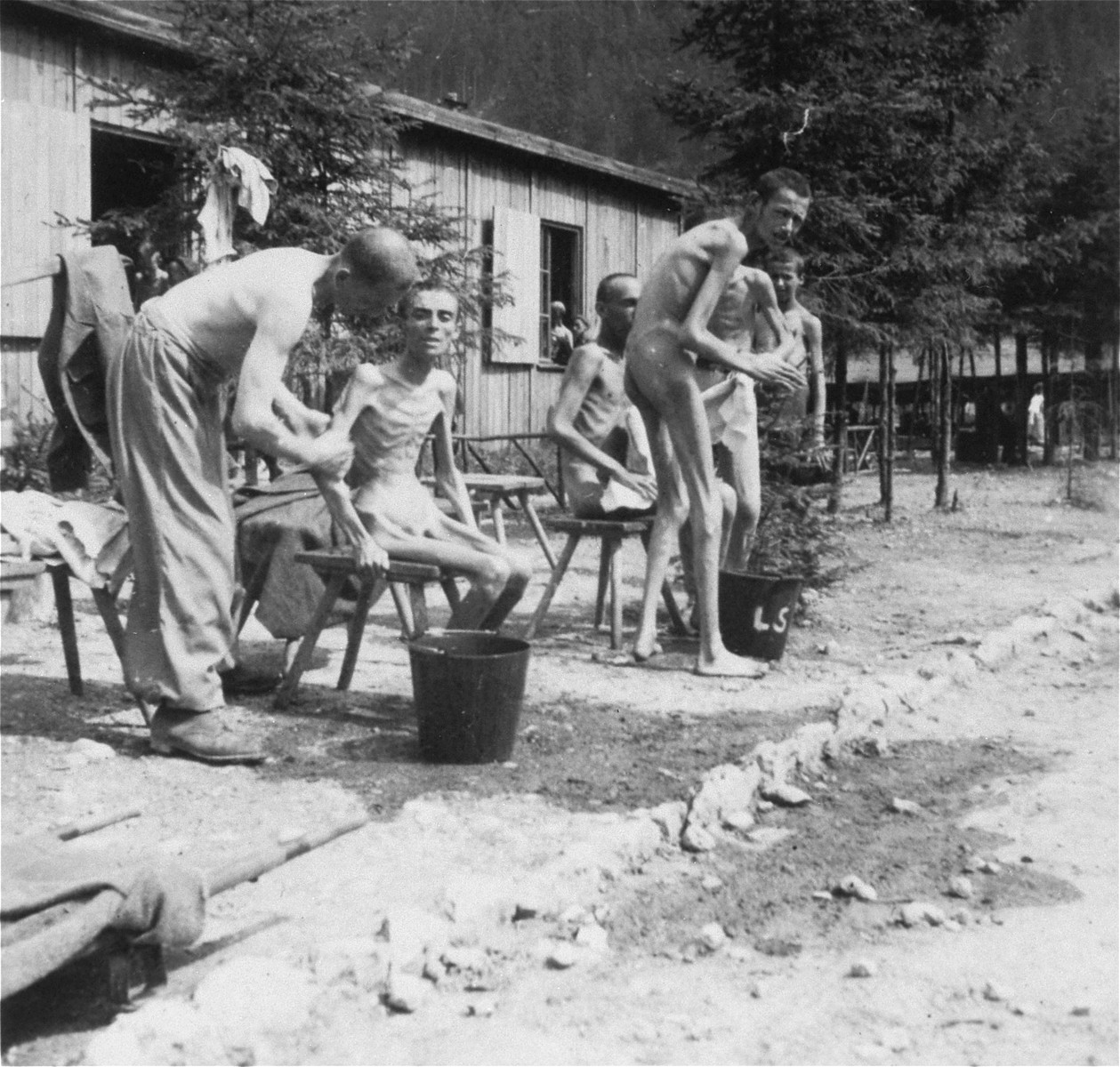 Survivors bathing after liberation, but prior to the installation of a portable shower unit by personnel of the 30th U.S. Army Field Hospital.