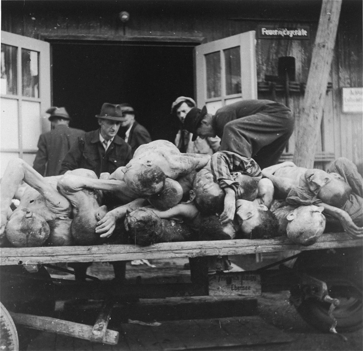 Austrian civilians load the bodies of Ebensee prisoners onto a cart for burial.