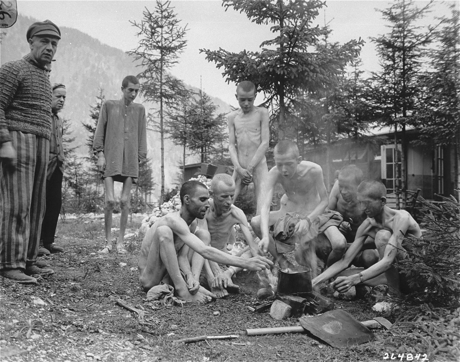 A group of emaciated survivors prepare a meal on an open fire in the newly liberated Ebensee concentration camp.    Among those pictured is Josef Szuyt, the former clerk of barracks 16.