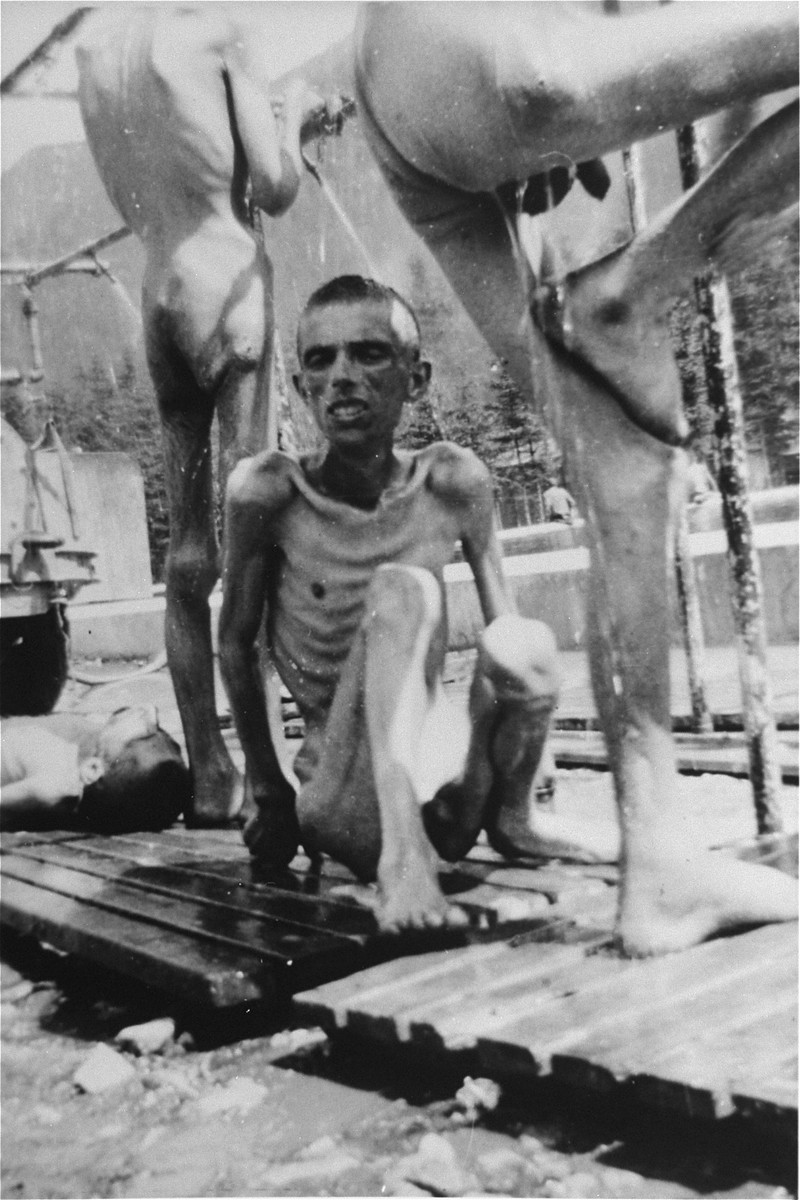 Emaciated survivors from hospital barracks 2 (for Jews) in  Ebensee use a portable shower unit set up for them by personnel of the 30th U.S. Army Field Hospital.