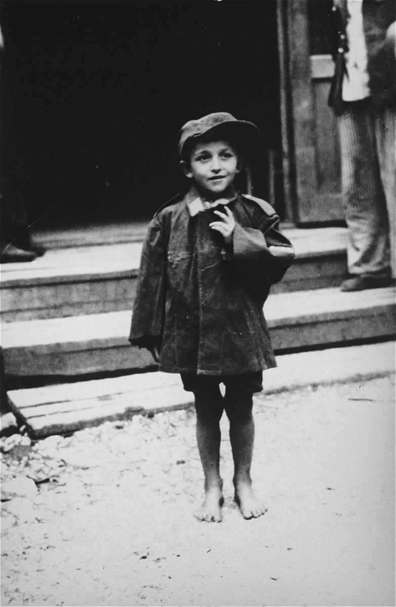 A child survivors stands in front of a barracks in the newly liberated Ebensee concentration camp.