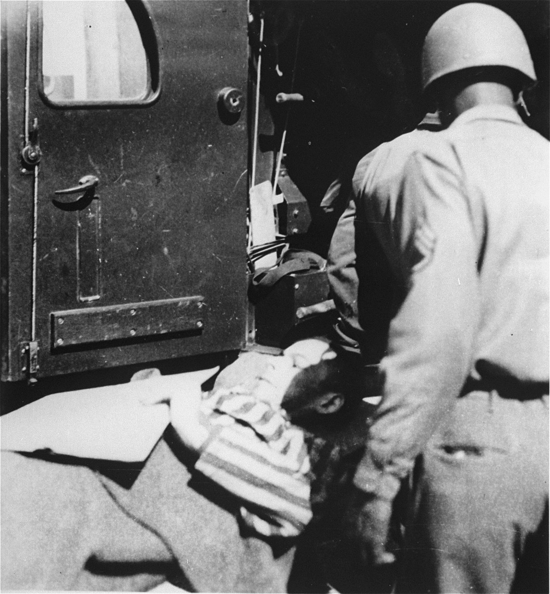 A survivor from the concentration camp at Ebensee is loaded onto an ambulance for transportation to the 139th Evacuation Hospital for medical treatment.