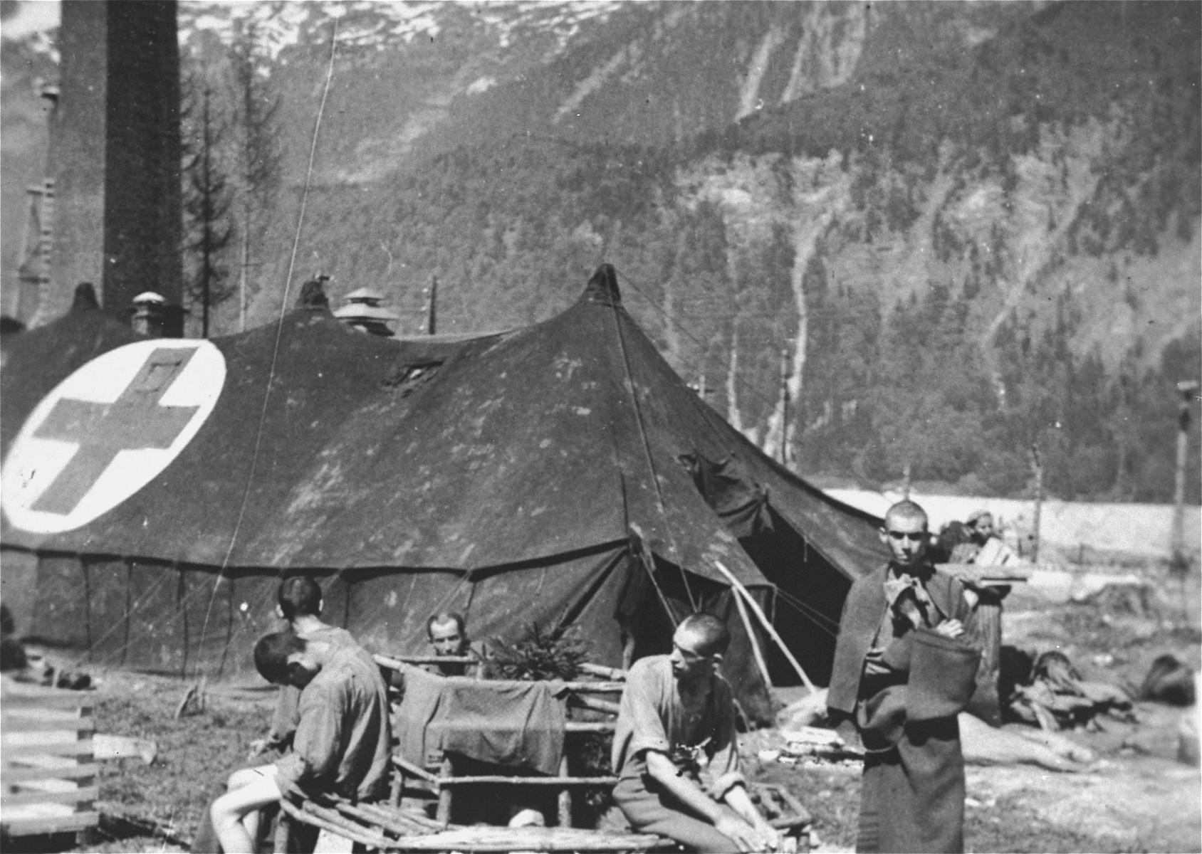 Survivors rest outside one of the tents of the 30th Field Hospital, set up by the U.S. Army in the Ebensee concentration camp.