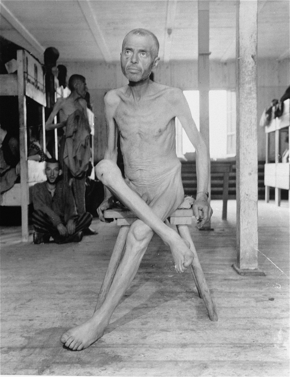 An emaciated Hungarian Jewish survivor sits on a stool in the infirmary barracks for Jewish prisoners in the Ebensee concentration camp.