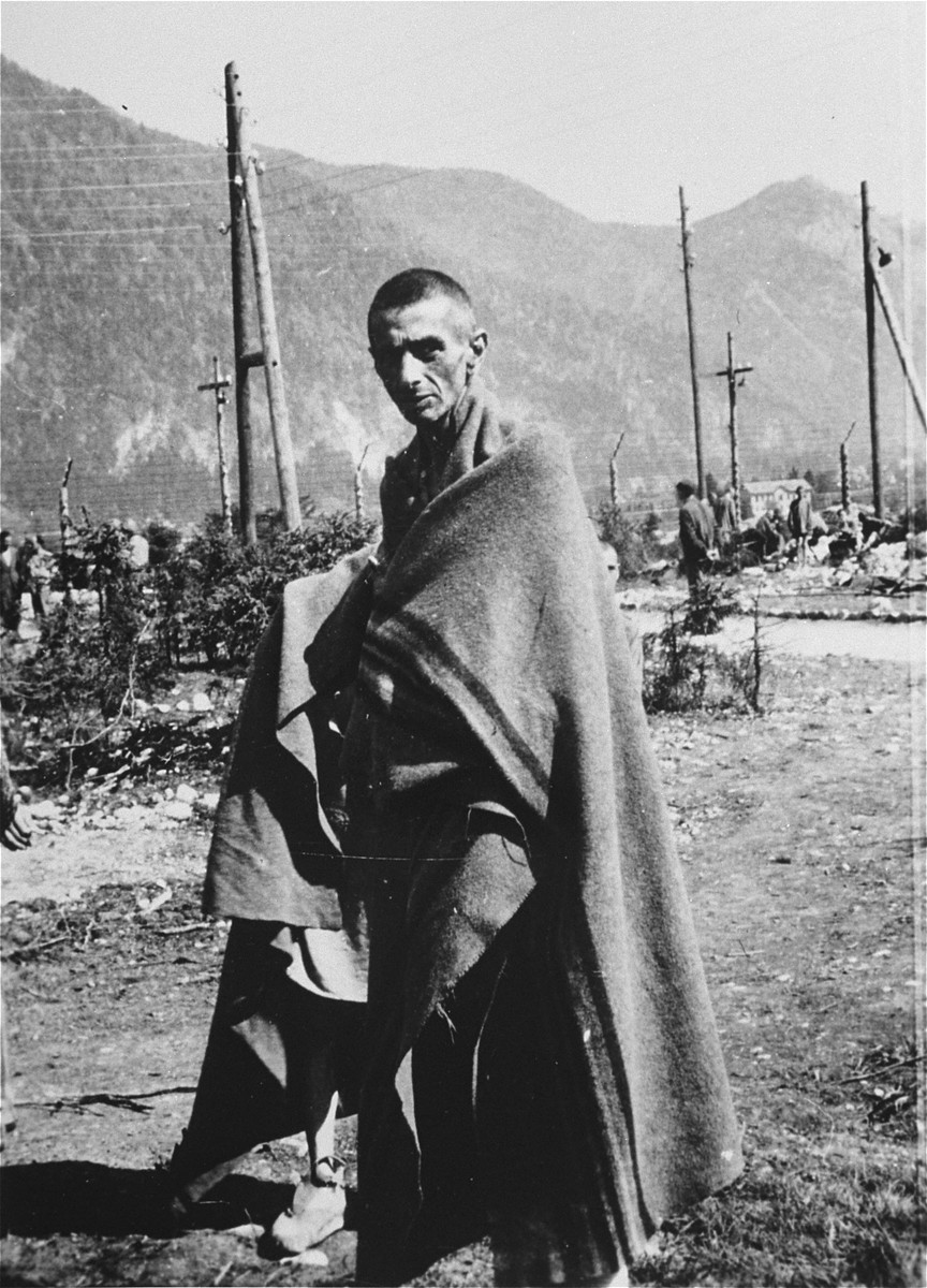 An emaciated survivor stands outside wrapped in a blanket in the Ebensee concentration camp.