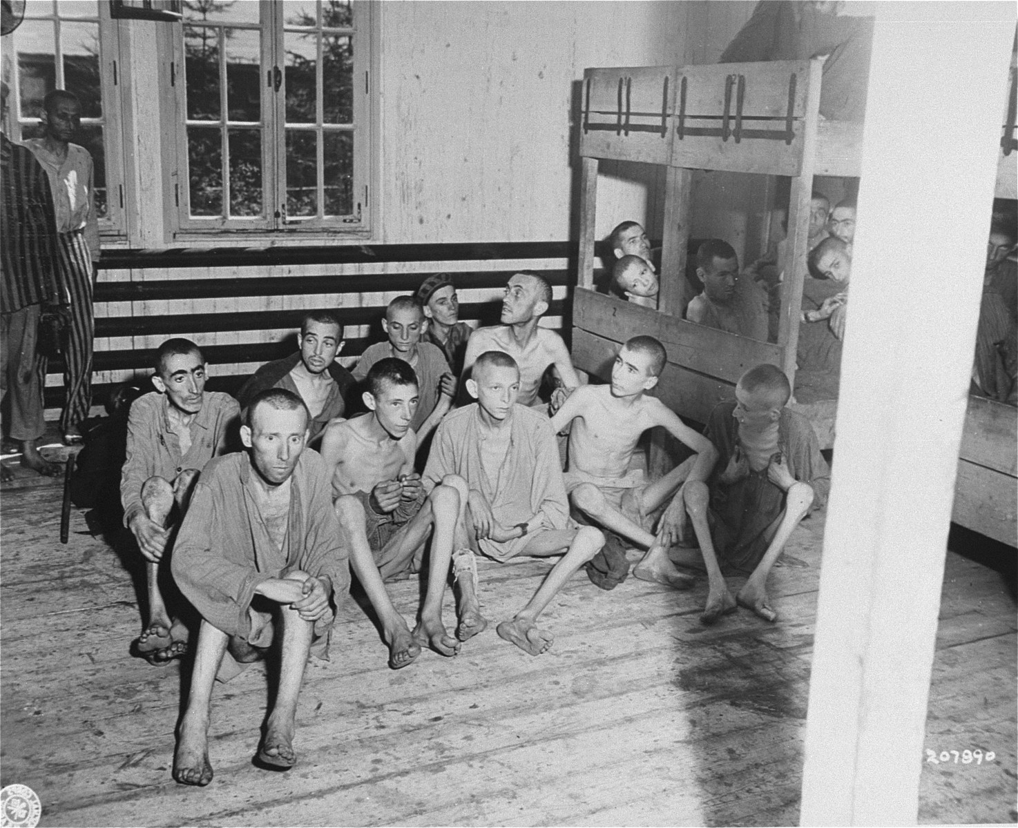 A group of emaciated survivors in the infirmary barracks for Jewish prisoners in the Ebensee concentration camp.  Among those pictured is George Havas (front row, second from the right).