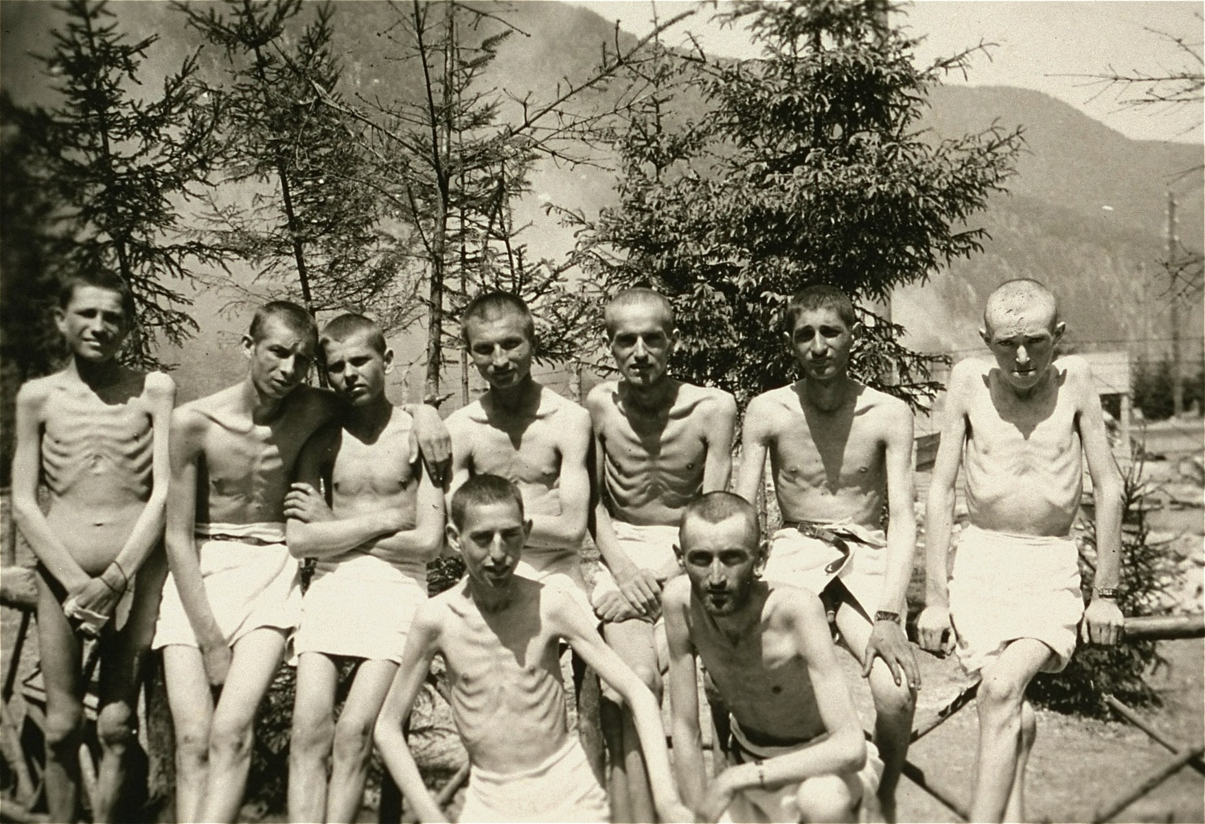 Group portrait of Ebensee survivors after having showered in the portable shower units installed in the camp by personnel of the 30th U.S. Army Field Hospital.