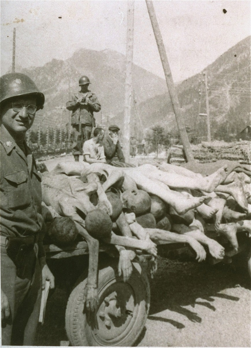 An American colonel poses next to a wagon loaded with the bodies of former prisoners at the newly liberated Ebensee concentration camp.
