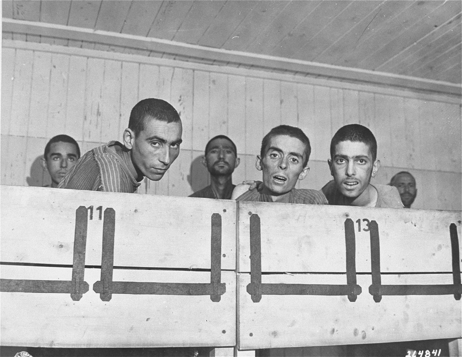 Survivors look out from the upper tier of a bunk in the infirmary barracks for Jewish prisoners in the Ebensee concentration camp.