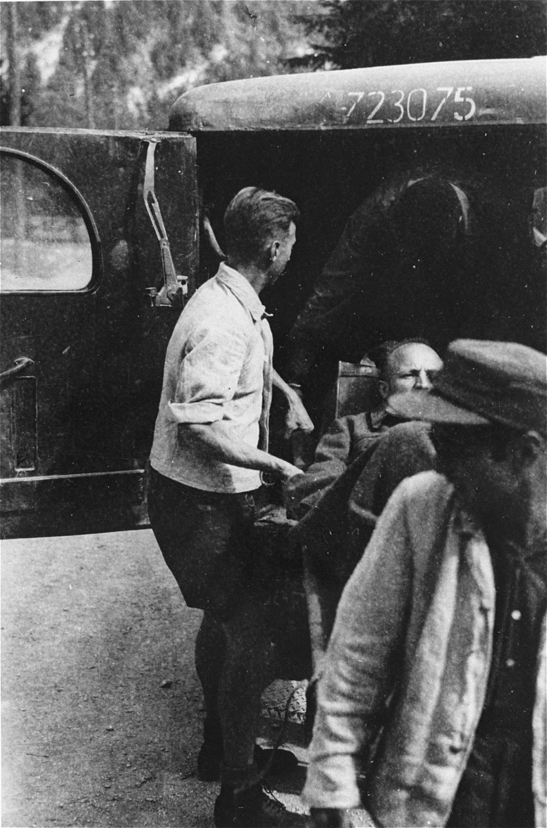 A survivor from Ebensee is loaded onto an ambulance by Austrian personnel for transportation to the 139th Evacuation Hospital for medical treatment.