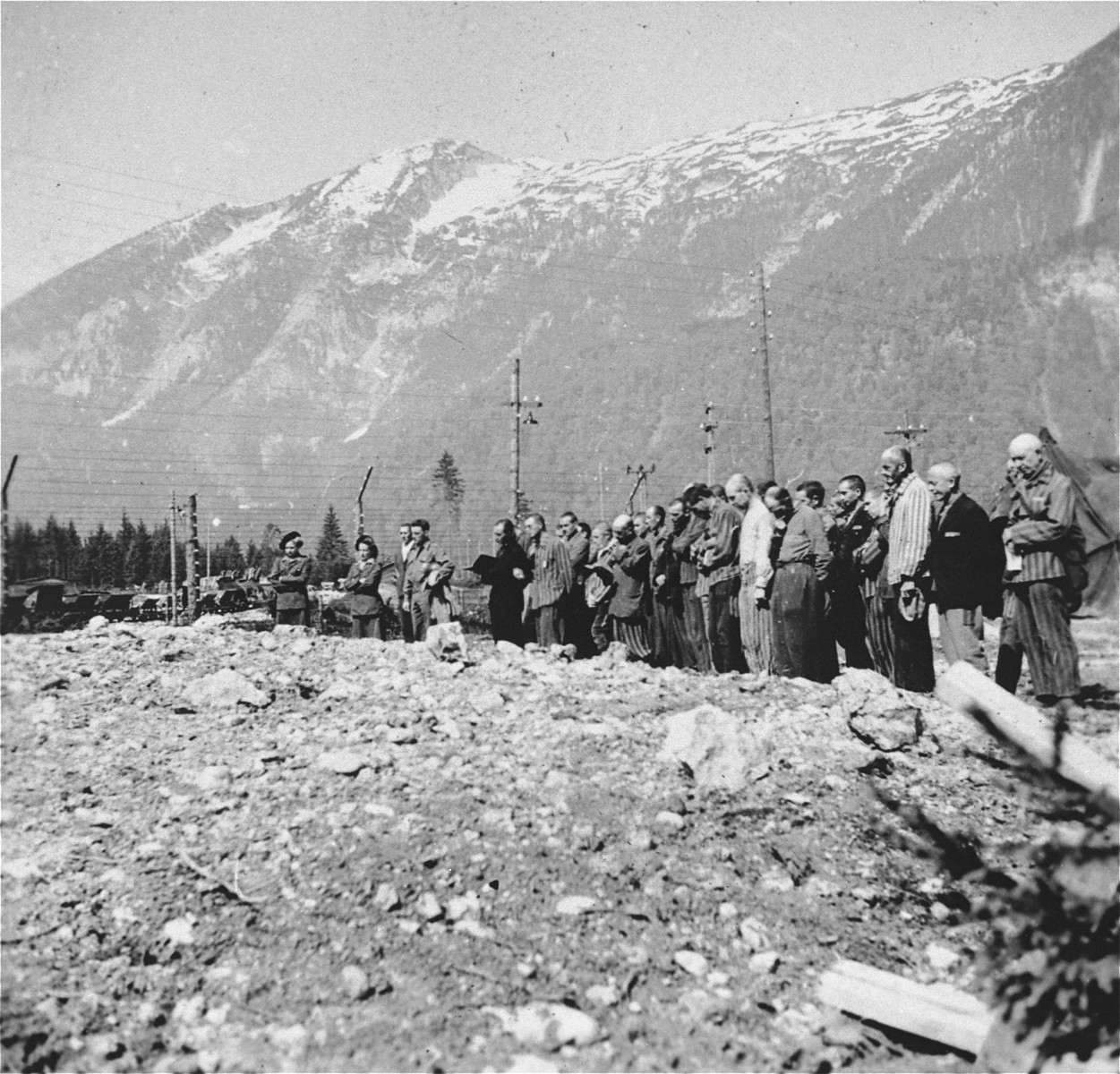 Survivors and military personnel in Ebensee attend a funeral ceremony at the edge of a mass grave holding some 1500-2000 bodies.