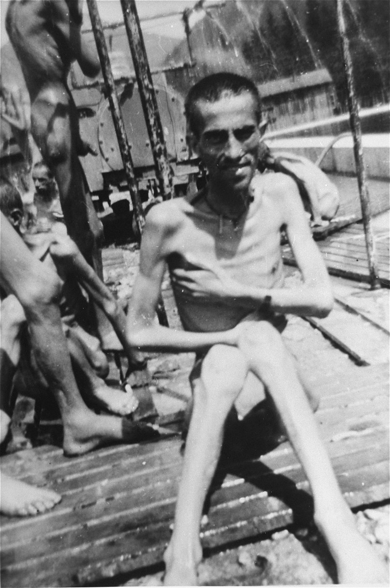 An emaciated survivor sits by a portable shower set up by the 30th U.S. Army Field Hospital two days after liberation.  He had been in the hospital barracks 2 (for Jews) in Ebensee, a sub-camp of Mauthausen, which was liberated by a unit of the 3rd Cavalry Recon. Sqd., U.S. Third Army, on 6 May 1945.