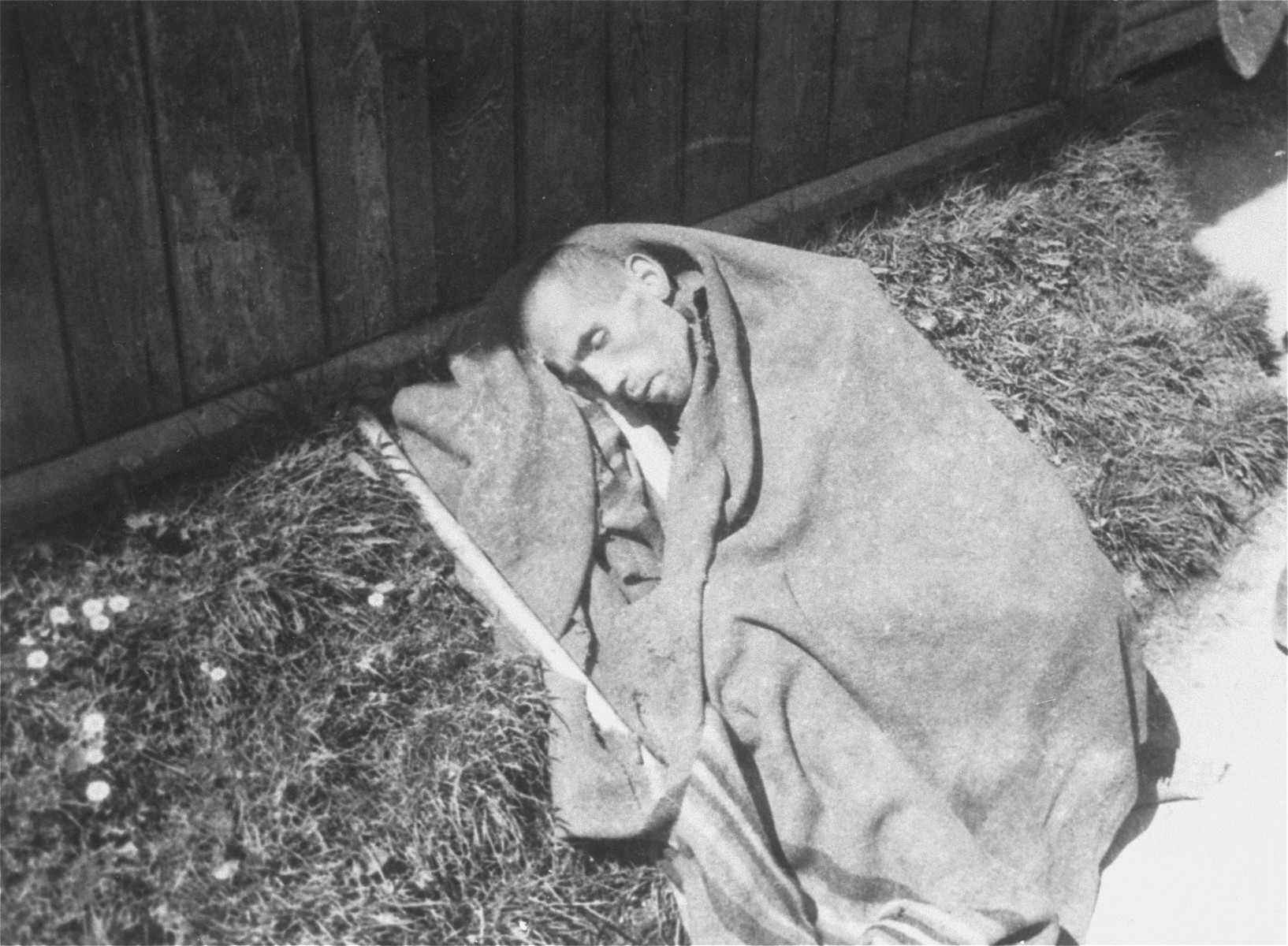 A survivor who is wrapped in a blanket lies outside a barracks in the newly liberated Ebensee concentration camp.
