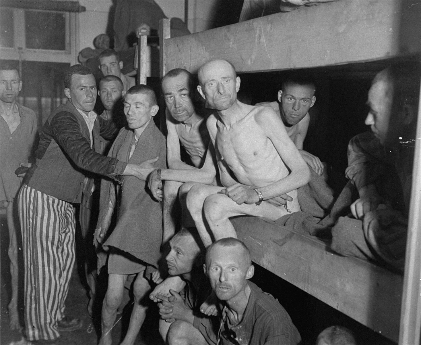 Emaciated survivors sit in bunks in one of the infirmary barracks in the Ebensee concentration camp.  Among those pictured is Edmond-Jean Remy, sitting, fourth from the right in the bunk.  Also pictured is Arnold Forner (Fornal), sitting on the bunk,  fourth from the right.