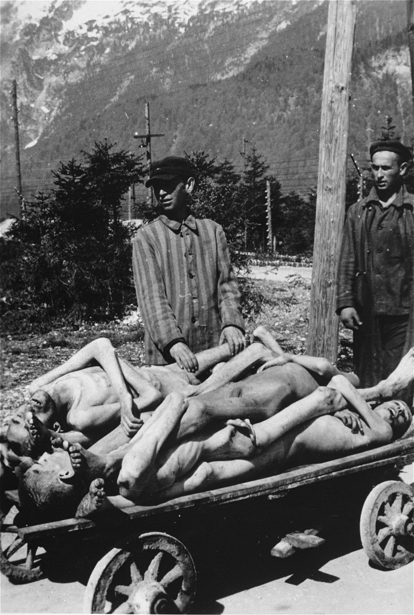 Survivors in the Ebensee concentration camp stand next to a cart stacked with the bodies of former prisoners.