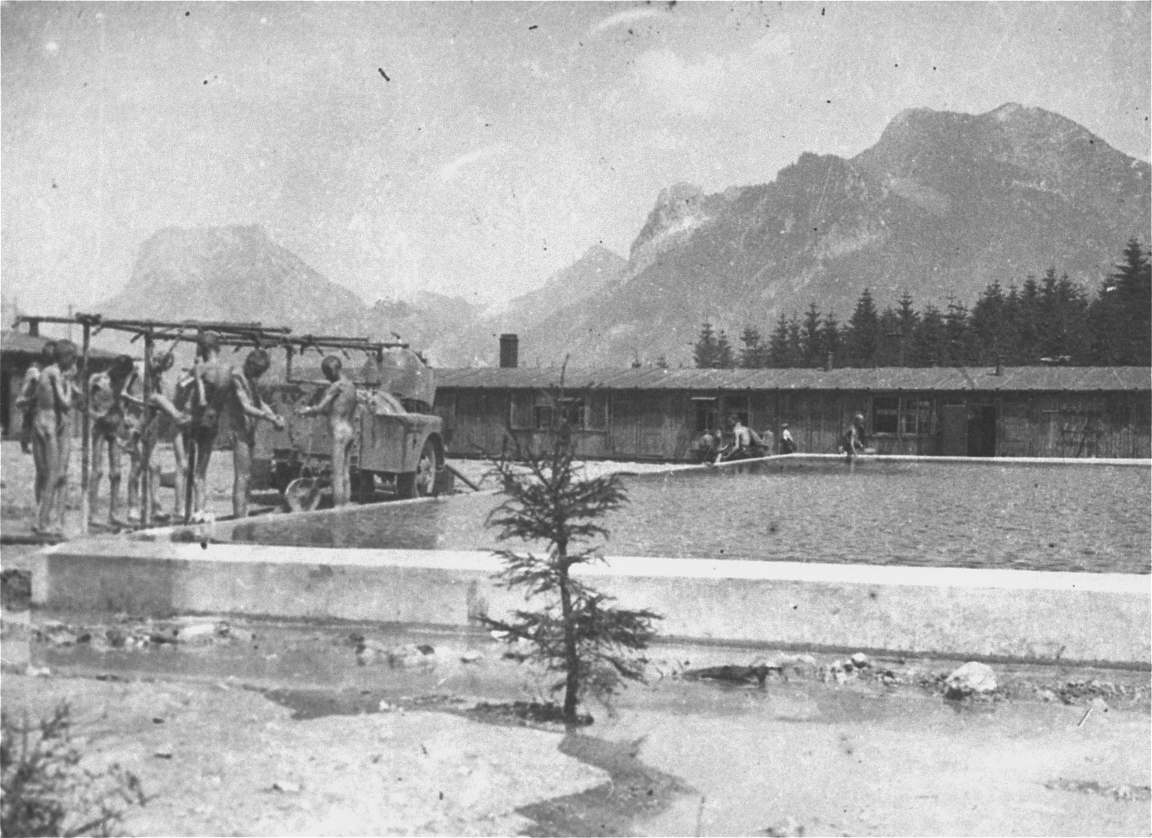 Survivors in the Ebensee concentration camp wash themselves at a portable shower installed by American personnel from the 30th U.S. Army Field Hospital.